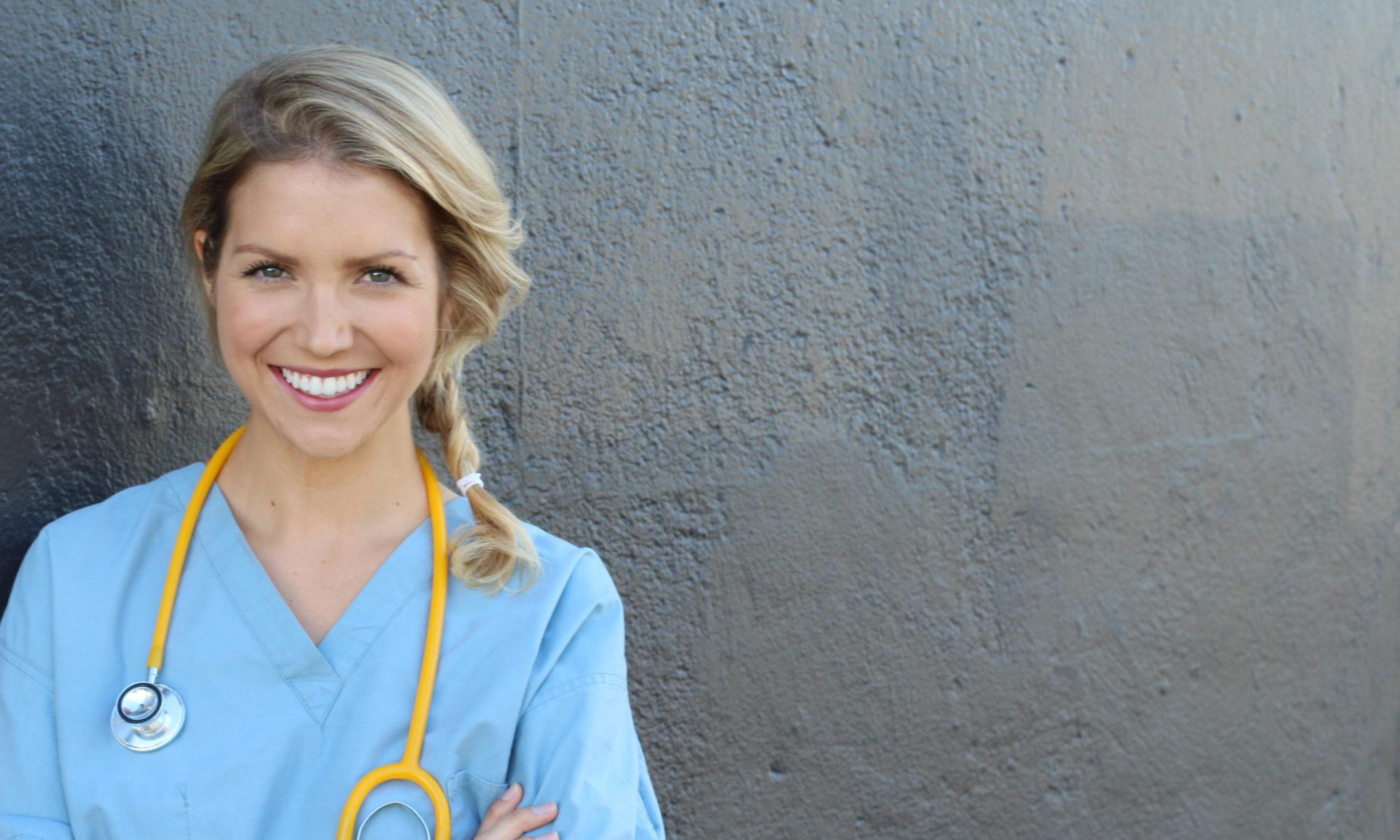 Junge lächelnde Ärztin mit blauen Kittel und Stethoskop