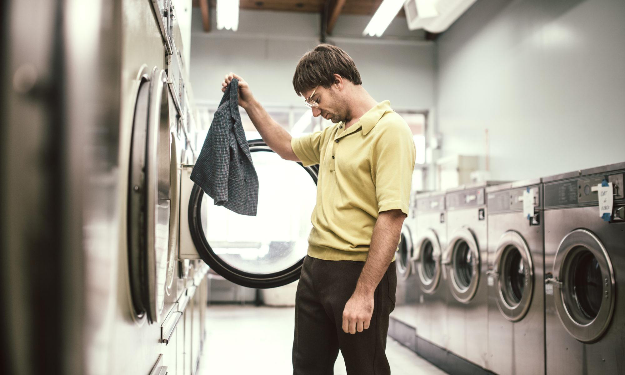 Ein junger Mann im Waschsalon schaut sich seine eingegange Jacke an