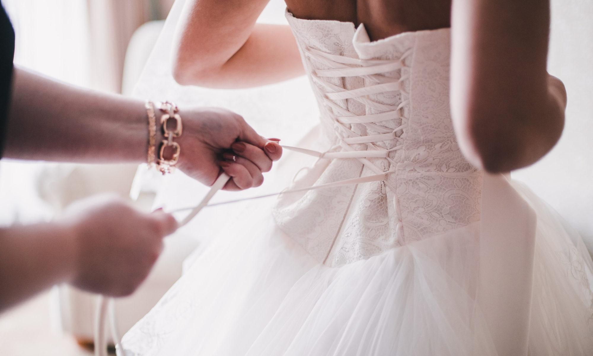 Hochzeitskleider im Hintergrund im Vordergrund wird der Braut ins Hochzeitskleid geholfen