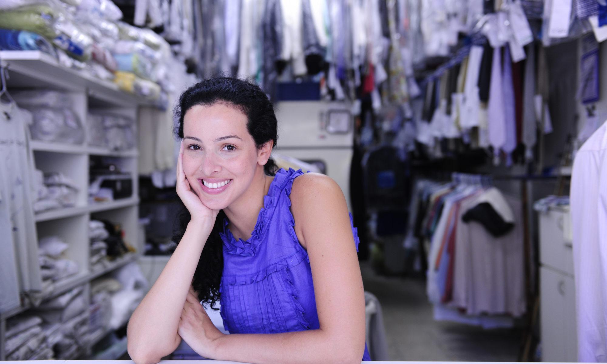 Glückliche Angestellte an der Theke einer Kleiderreinigung